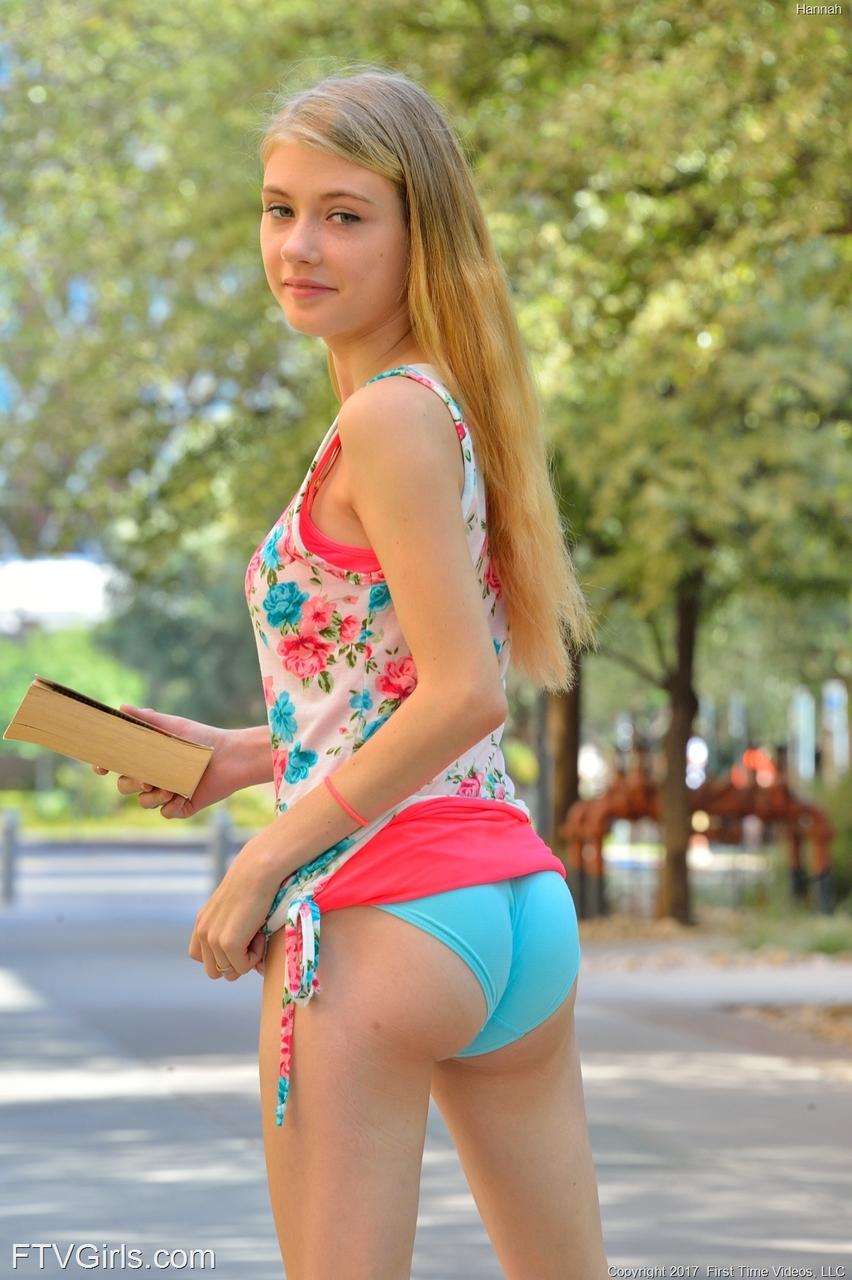 Молодая девушка, сидя на улице на скамейке, ласкает пальцами вагину