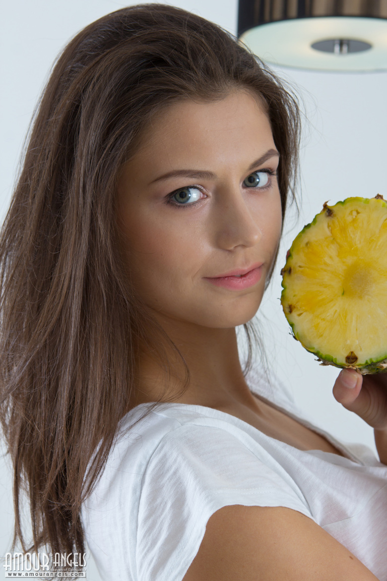 Обнажённая девушка с ананасами в руках раздвигает половые губы на столе