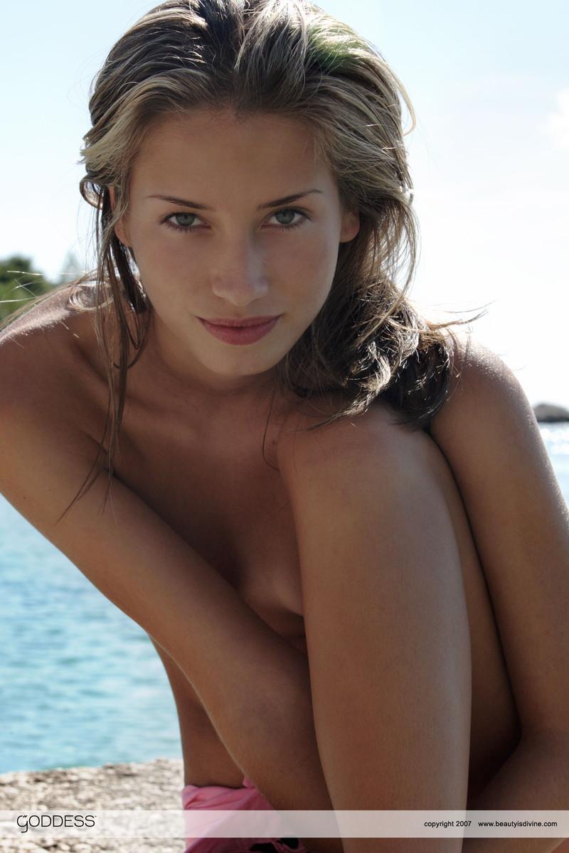 Стройная девушка с торчащими сосками в трусиках фотографируется около океана