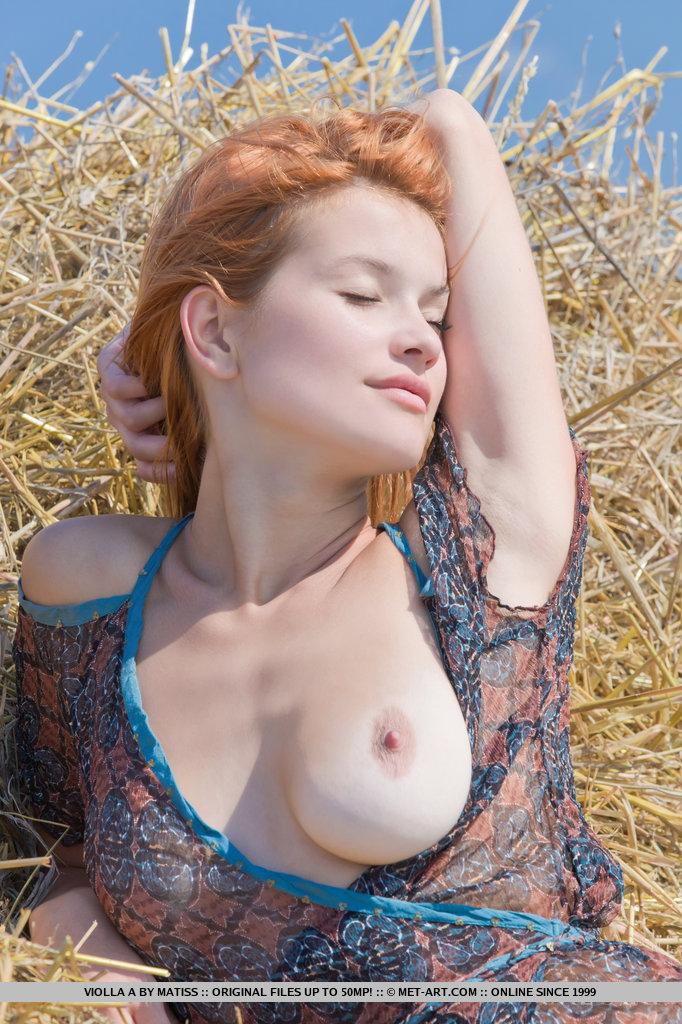 Пышногрудая рыжая стерва раздвигает ноги, показывая бритую пилотку на сене