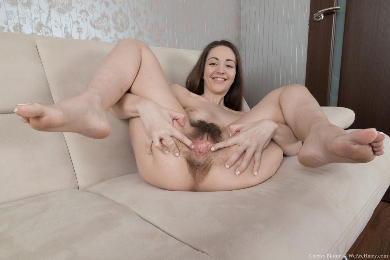 Девушка крупным планом раздвигает половые губы волосатой промежности