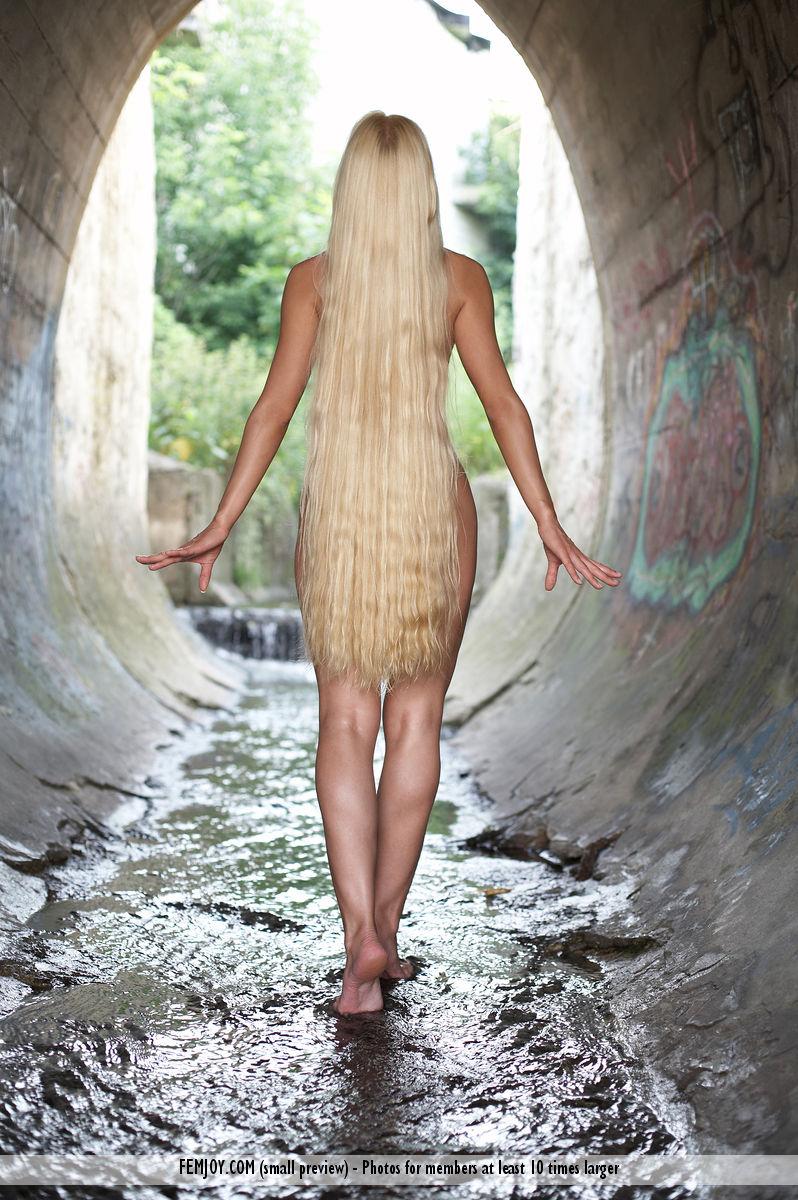 Длинноволосая блондинка на природе позирует голой пилоткой на фотосессии