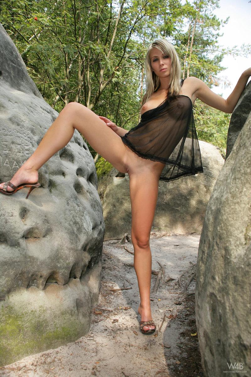 Грудастая девушка на каблуках  поднимает ногу около камня, показывая дырочки