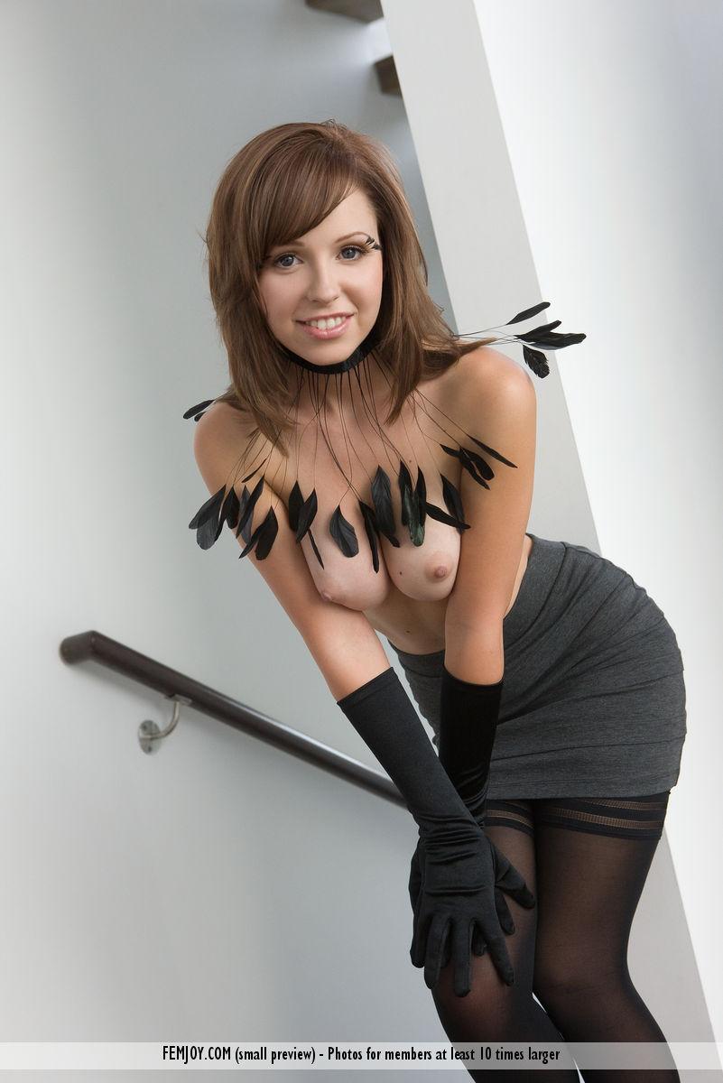 Сисястая девушка с ожерельем из перьев фотографируется голая в чулках