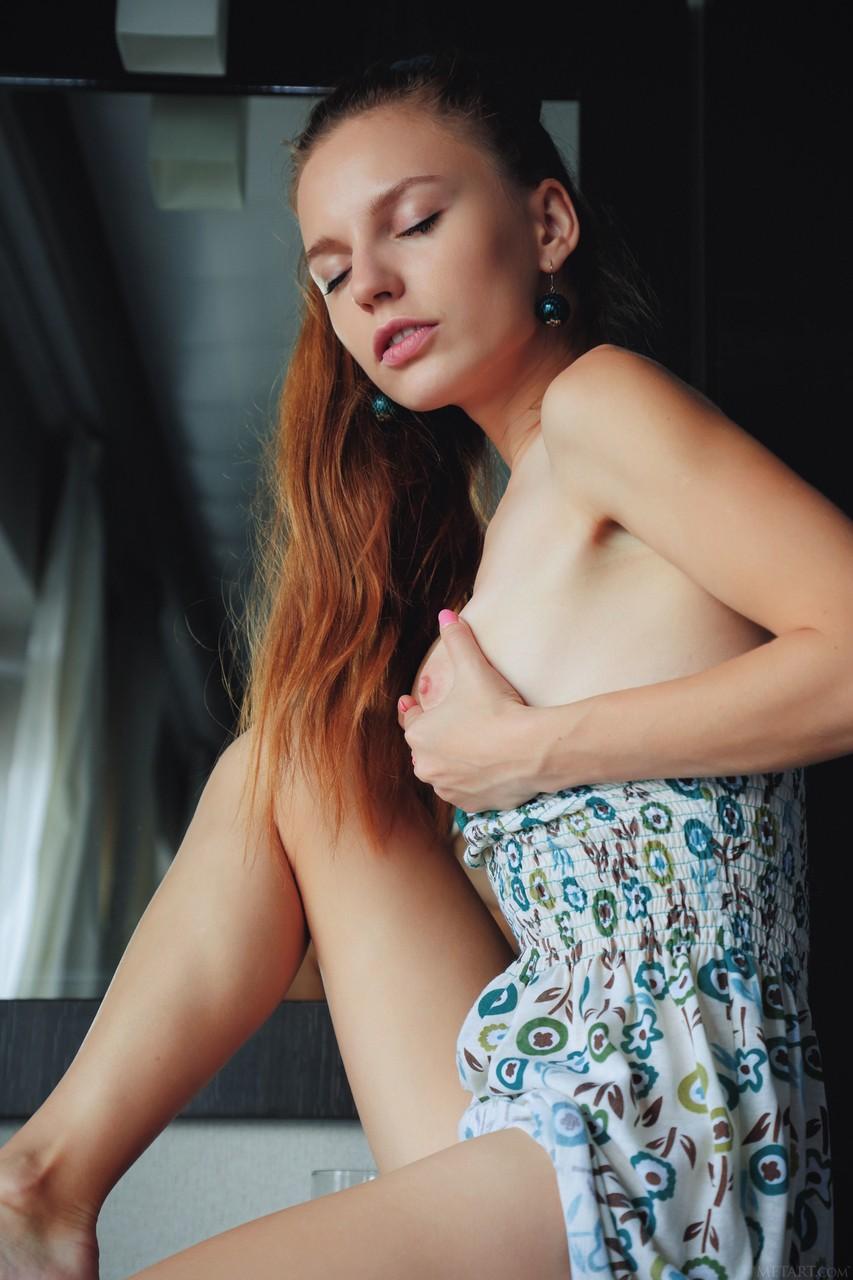 Худая девушка показывает набритую пилотку, поднимая платье вверх