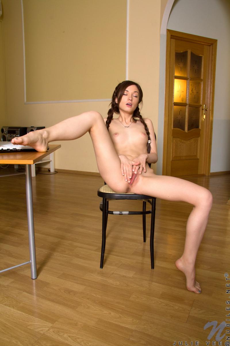 Молодая девушка села на стул и мастурбирует клитор перед другом