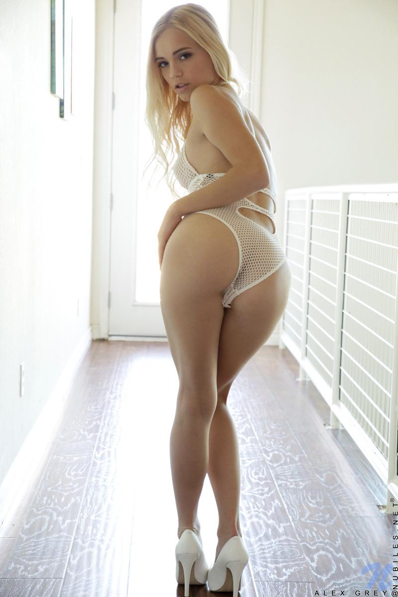 Стройная блондинка на каблуках, сидя на лестнице, дразнит своей пилоткой