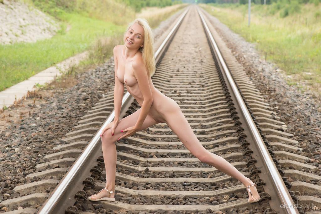 Блондинка с плоским животом и с голой промежностью стоит раком на путях