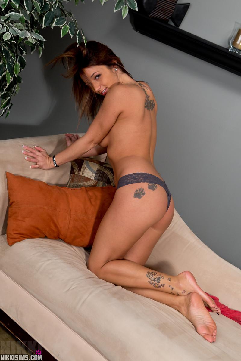 Похотливая татуированная девушка, сняв лифчик, ласкает дойки руками