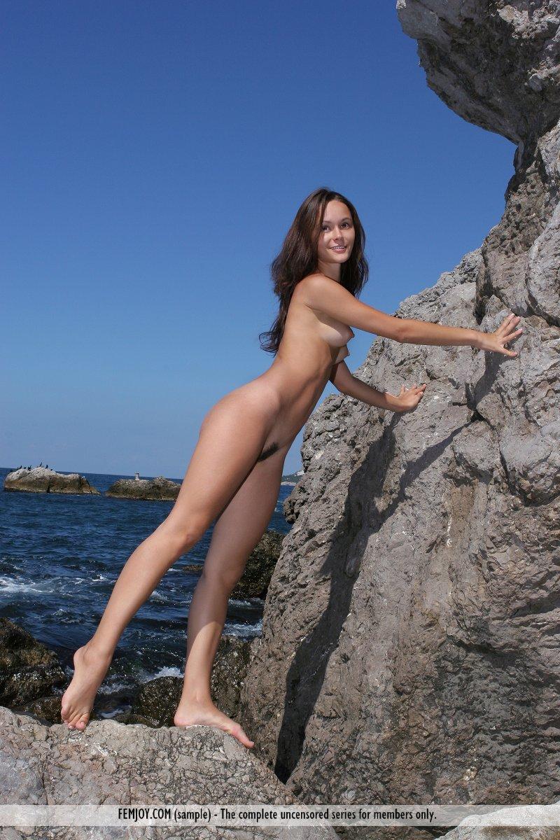 Стройная брюнетка с стоячими сосками фотографируется на берегу моря