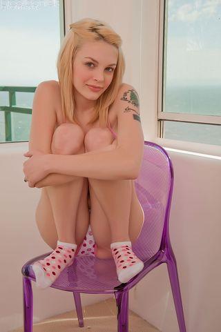 Похотливая блондинка сняла трусики и на стулике показывает свои дырочки